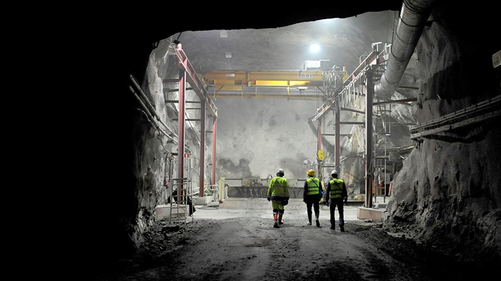 Three people pictured at an underground mine.