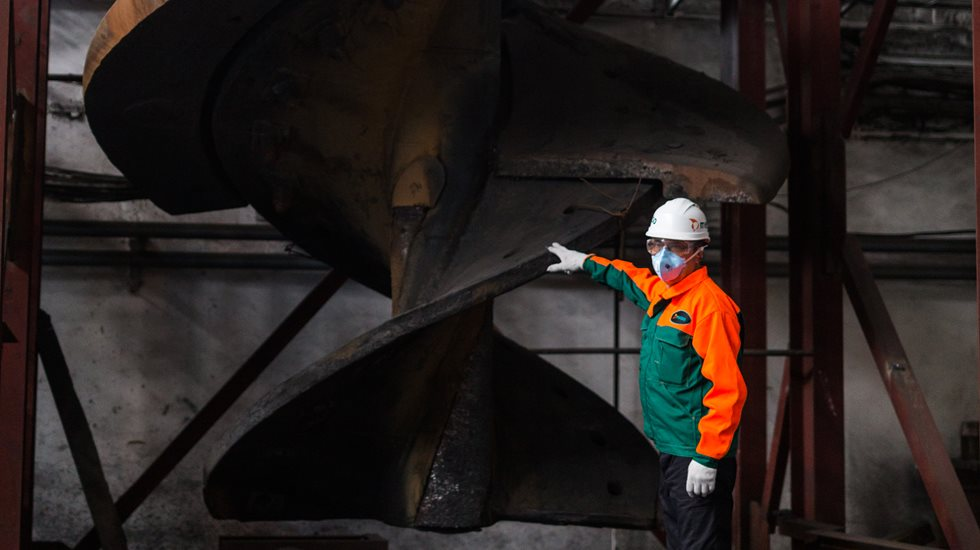 Metso employee points at a Vertimill refit part that can increase longevity