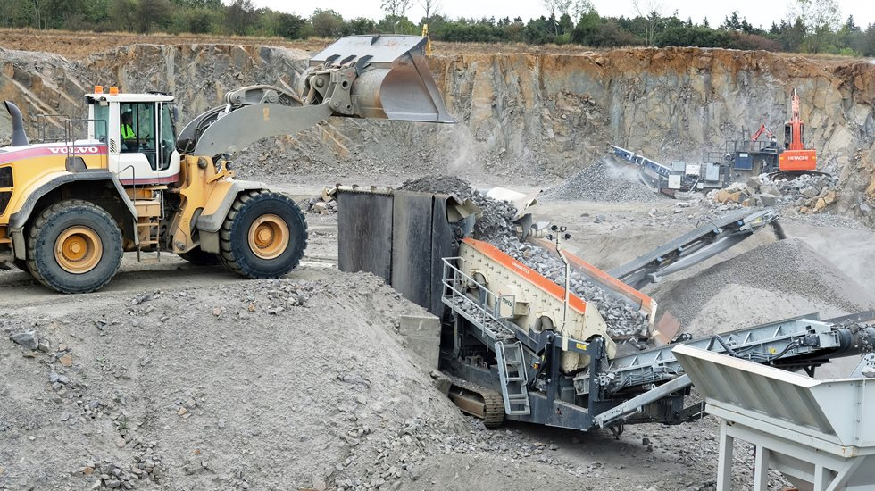 An excavator feeding a Lokotrack at a quarry.