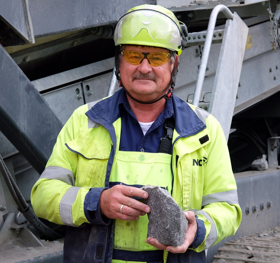 A man holding a rock in front of a Lokotrack.