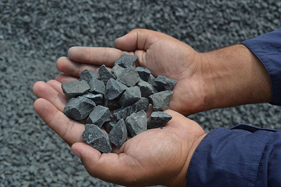Hands holding grey aggregate.