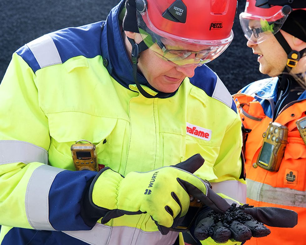 The dark ore that Jarkko Kettukangas is holding is crushed to 0-8 mm in four stages before arriving in the heap leach area.