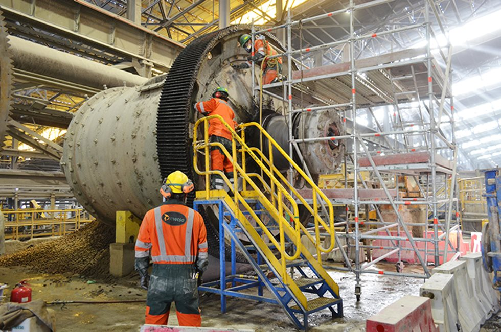 Maintenance personnel around a grinding mill at Codelco's site.