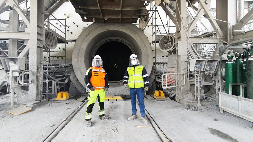 Two men in front of ball mill opening.