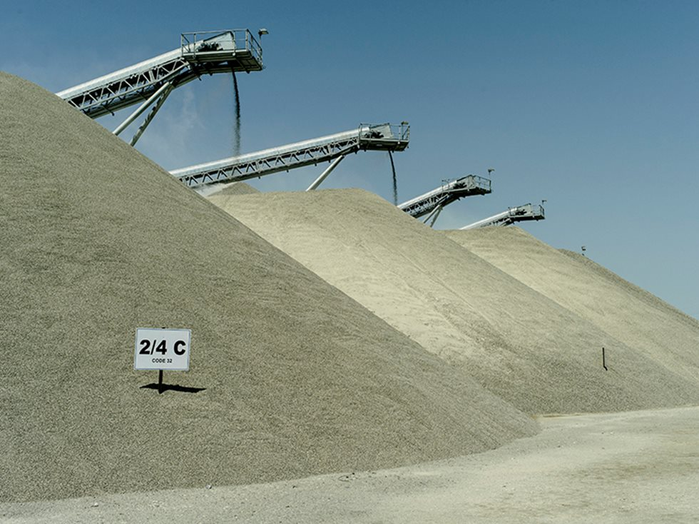 Three piles of processed aggregates with parts of conveyors peaking on top.