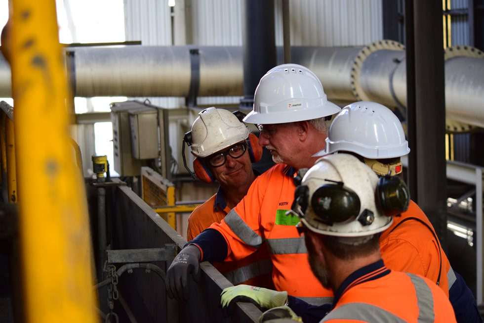 Four employees discussing at Glencore facility.